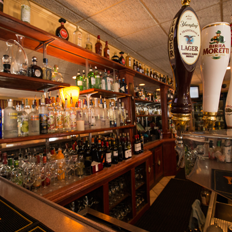 a close up of our beers on tap with the our extensive collection of spirits behind the bar